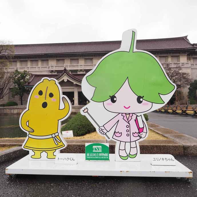 東京国立博物館の公式キャラクターである「トーハクくん」と「ユリノキちゃん」を形どった看板の写真です。東京国立博物館の入り口に立てかけられています。向かって左側が高さ50cmのトーハクくん、右側が高さ1mのユリノキちゃんです。トーハクくんは館所蔵の「埴輪 踊る人々」を模した埴輪、ユリノキちゃんは本館前の「ユリノキ」の花をモチーフにした女の子です。