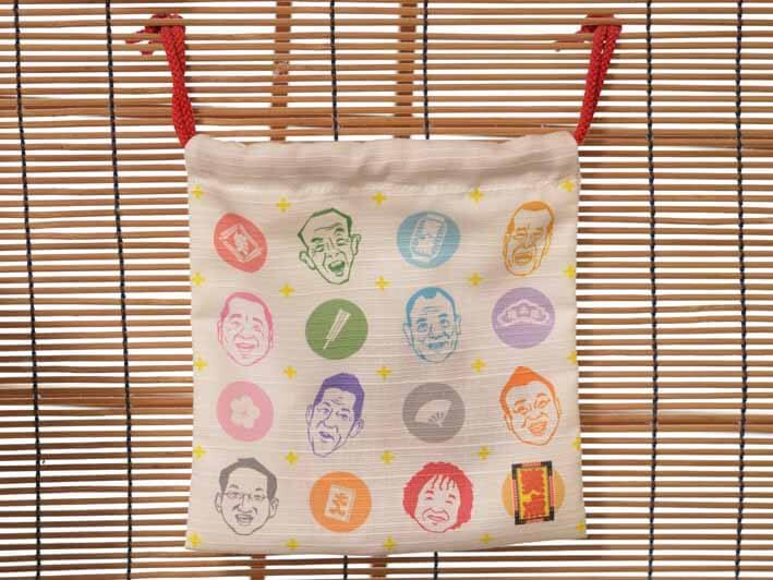 「笑点商店」で購入した巾着の写真です。白い生地にメンバーの似顔絵が着物の色で描かれています。大きさは縦横20cmで、赤いひもがついています。
