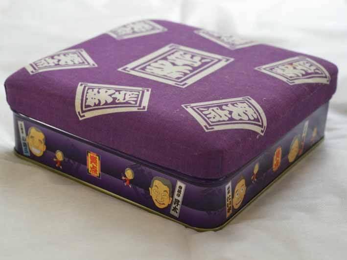 お菓子のケースの写真です。座布団を運んでいる山田隆夫さんにいただいたものです。縦横20cm、高さ10cmの大きさです。笑点の特製せんべいが入っていました。ケース全体が紫色です。蓋は笑点の座布団になっていて、白い文字で笑点と書かれています。お菓子を入れる部分は金属製で、出演者の似顔絵が描かれてしまいます。