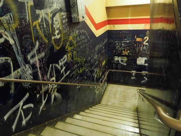 後楽園ホールの非常階段の壁に書かれた落書きの写真です。壁一面が落書きで埋まっています。