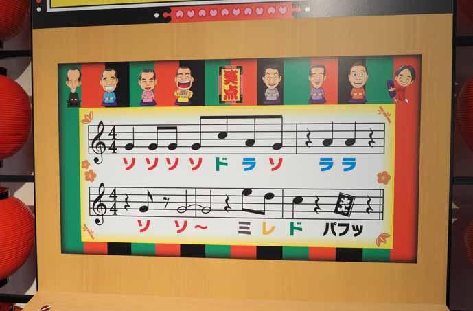 会場に設置されていた笑点のテーマ曲を奏でられるゲーム機の写真です。正面のボードにテーマ曲の楽譜が描かれています。音符には色がついています。手前には色のついたボタンがあります。ボタンを押すと音が出ます。音符と同じ色のボタンを押していくと笑点のテーマ曲を演奏できます。黒いボタンを押すと最後の「パフッ」という音が出ます。
