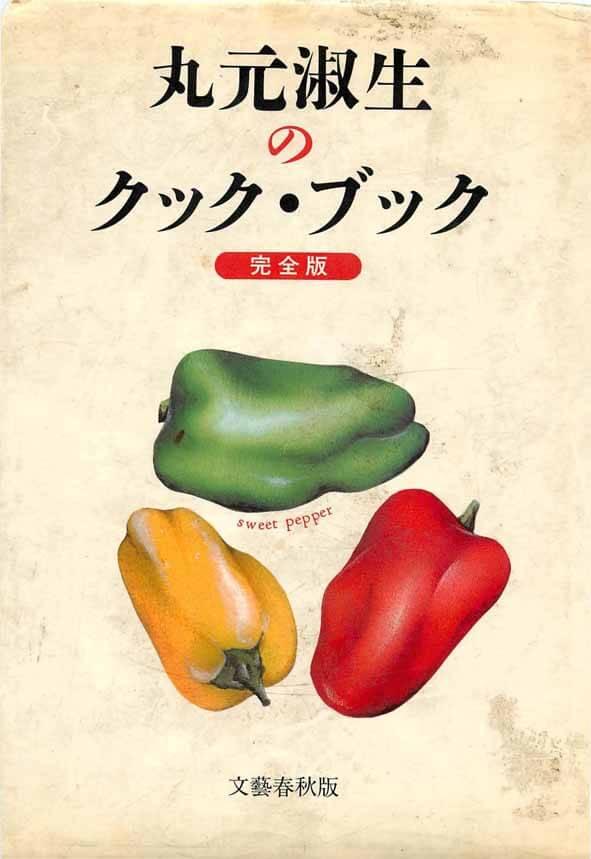 丸元淑生のクック・ブックという本の表紙です。緑、黄、赤色のピーマンの絵が描かれています。