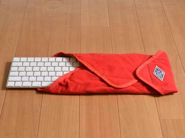 マジックキーボードをケースに入れた画像です。ケースは赤い布でできています。